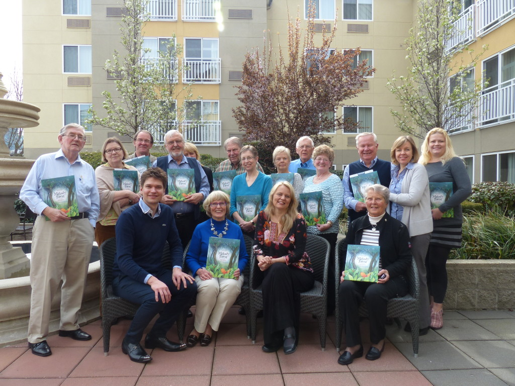 Trustees with their copies of Melody Forest, the children's book and CD produced by Finnish cellist Jussi Makkonen (seated, left). Pianist Ruusamari Teppo is seated second from right.
